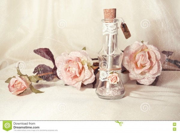 Wedding Invitation In A Glass Bottle And Pink Roses Stock Image